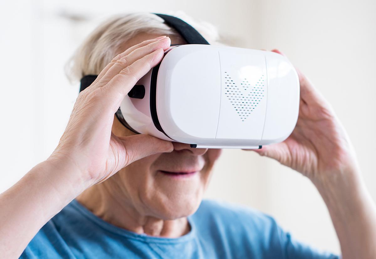 Happy senior man in t-shirt using virtual reality headset